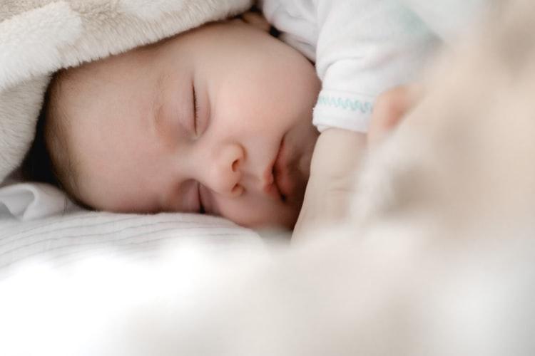 Bebe care doarme in pijamale de copii